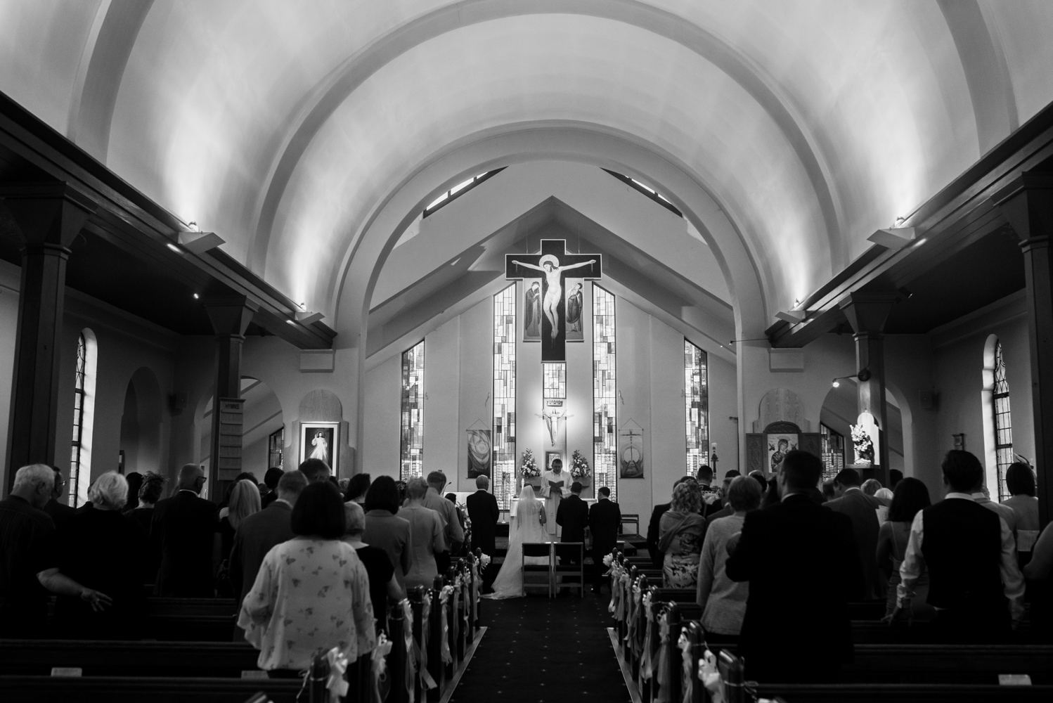 Black and white wide angle shot from the back of the church during the wedding ceremony