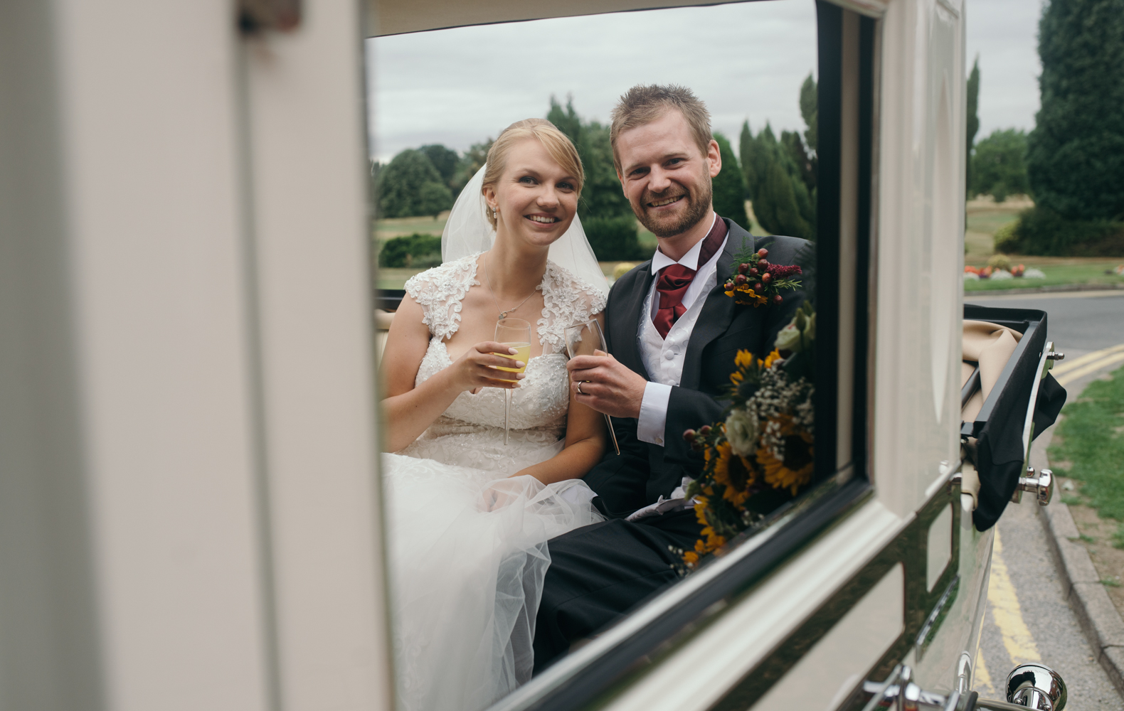 The bride and groom sitting in the back of the car having a cheeky glass of champers