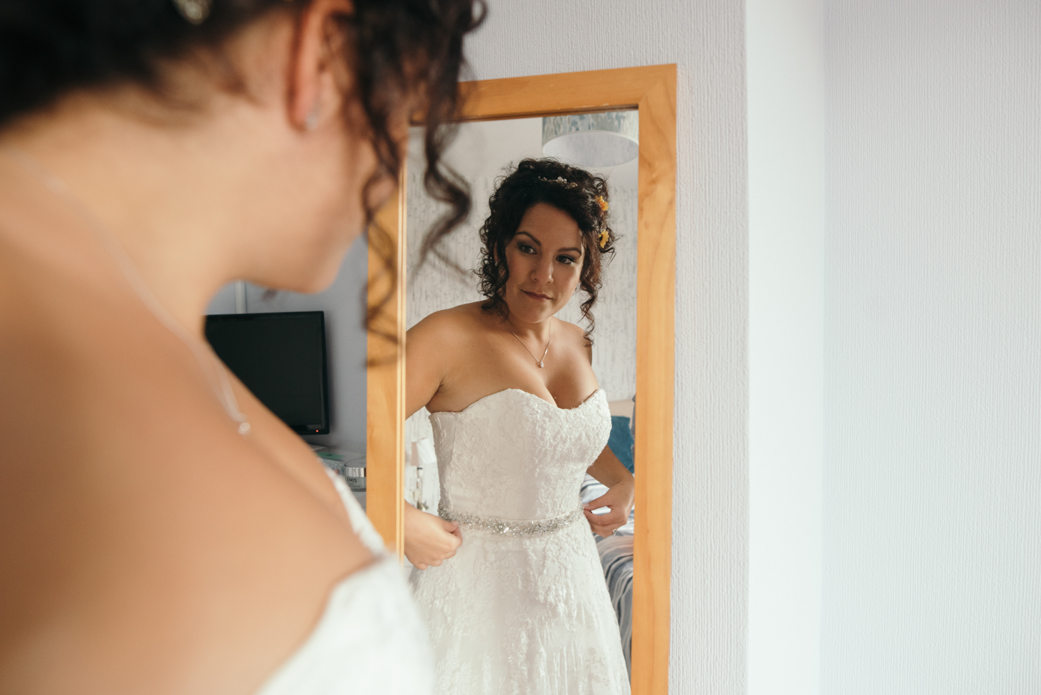Bride adjusts her dress in a mirror during bridal preparations