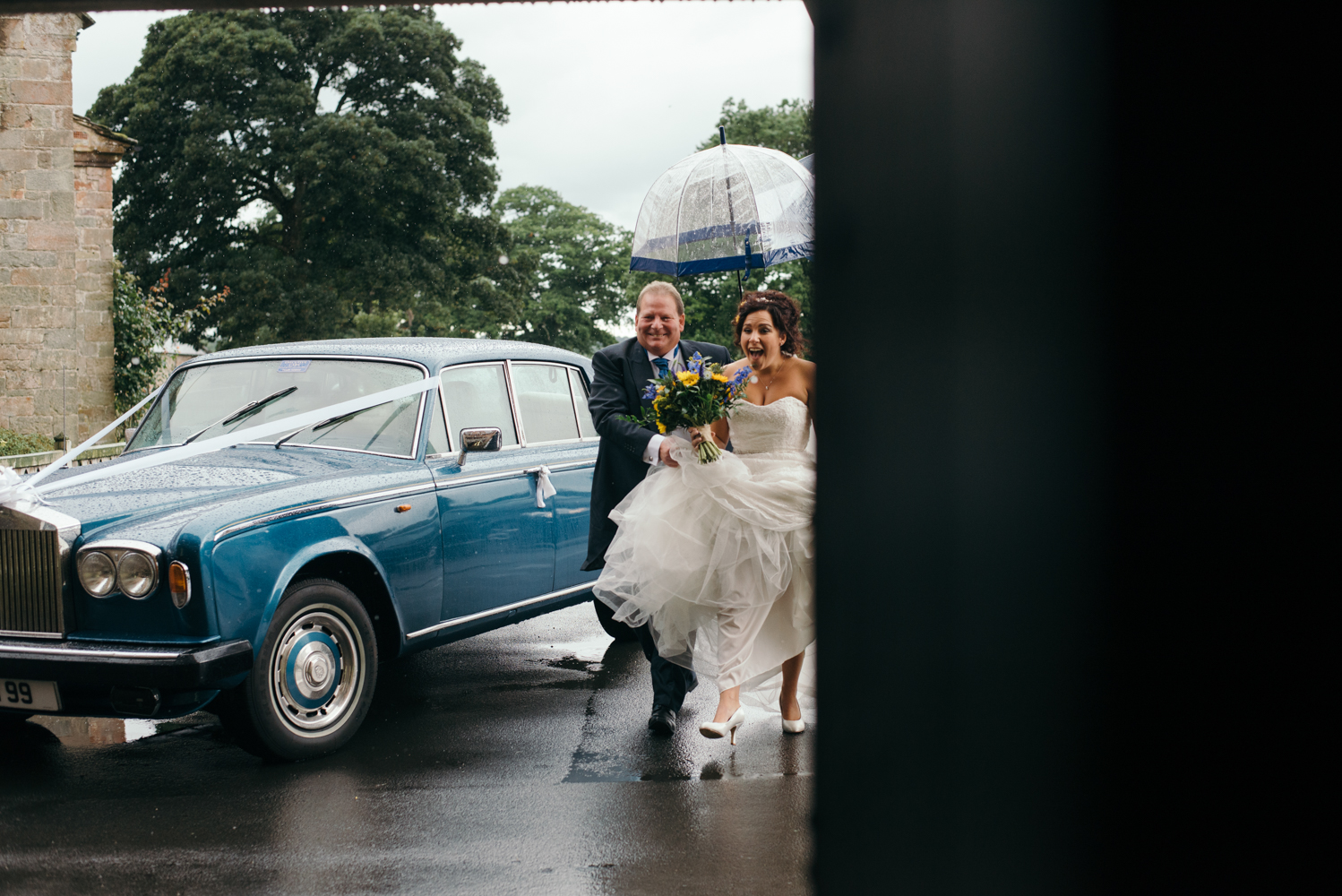 Bride and her father running into church out of the rain