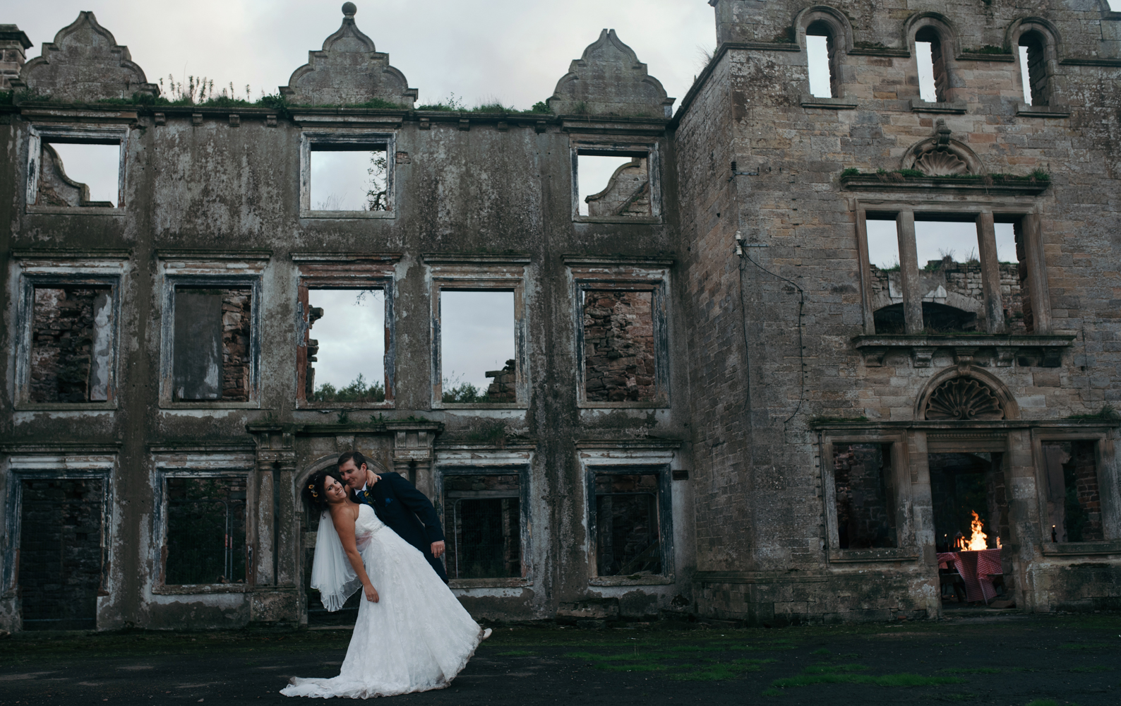 Bride and groom with the hall in the background