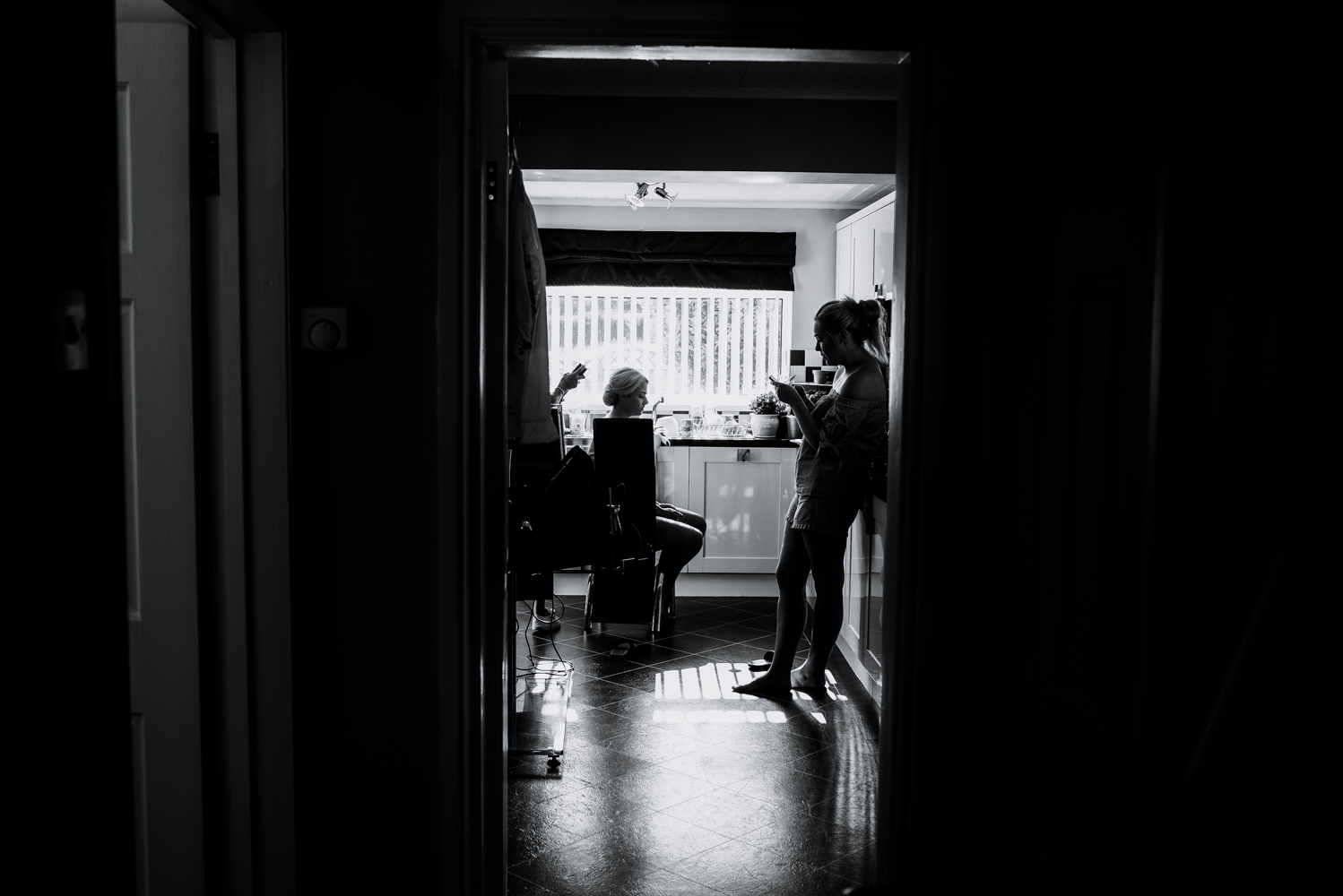 Black and white shot from the bottom of the hallway looking into the kitchen during bridal preparations