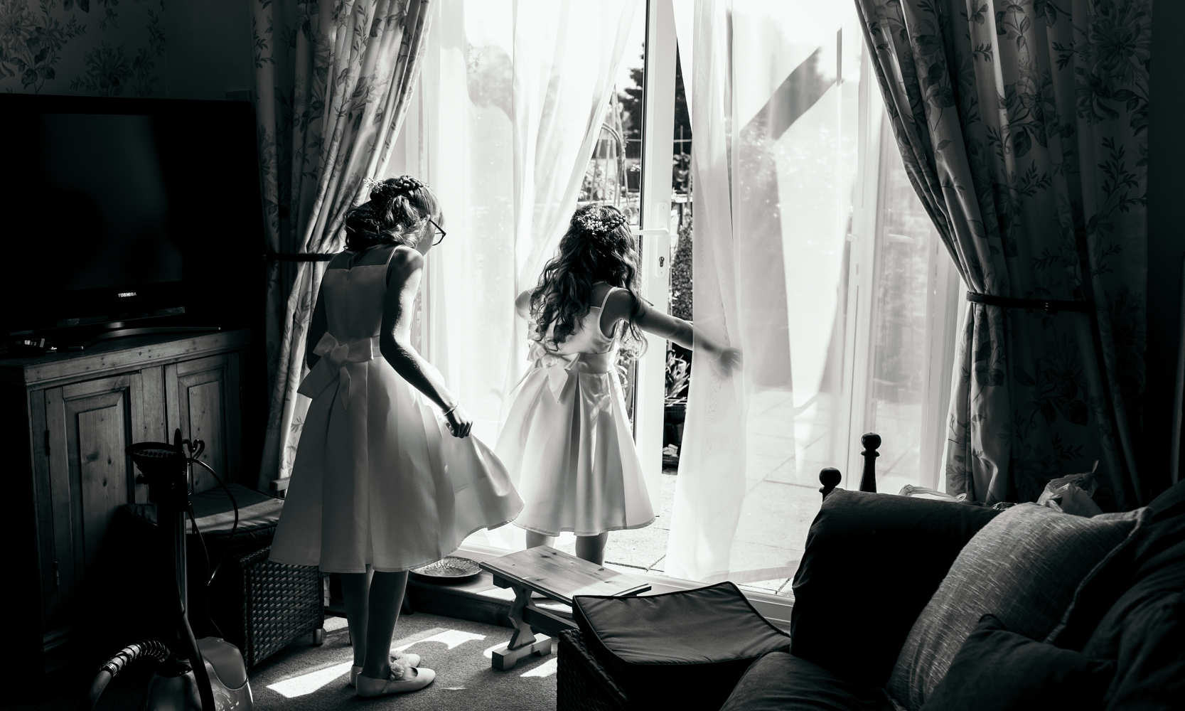 Black and white photo of two young bridesmaids playing during bridal preparations