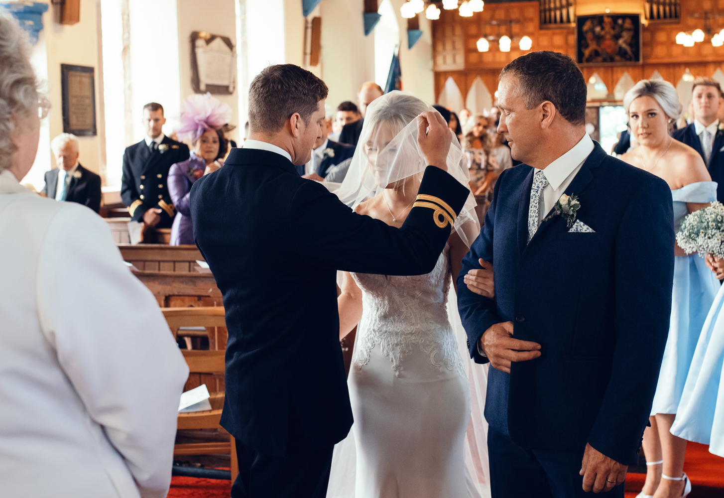 The groom removes the brides veil in church before the ceremony begins