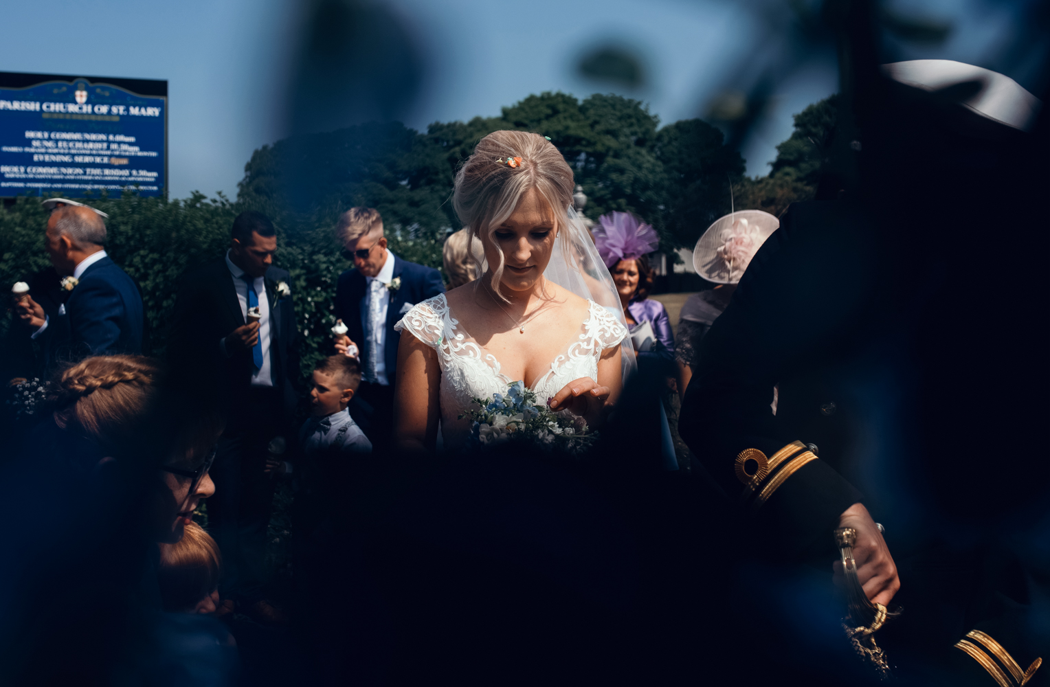 A photo of the bride through a wrought iron gate at the church after the ceremony