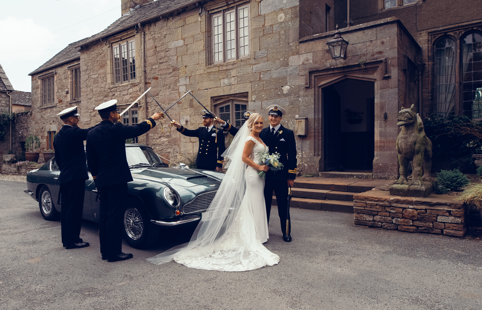 Guard of honour with the bride and groom and Aston Martin