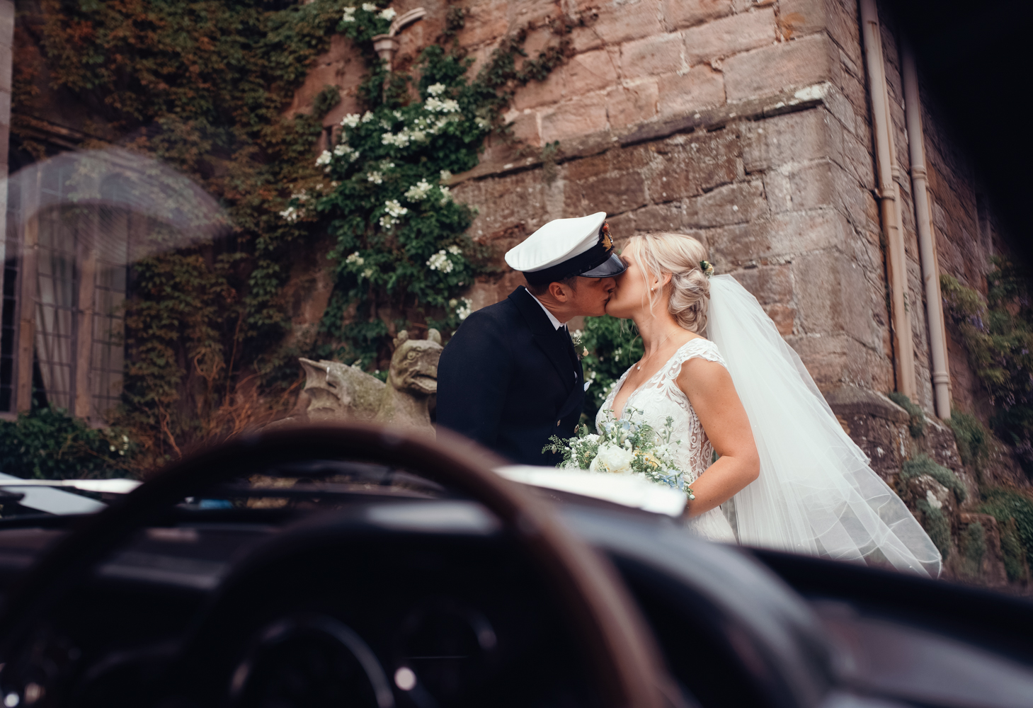 The bride and groom kissing through the front window of the Aston Martin