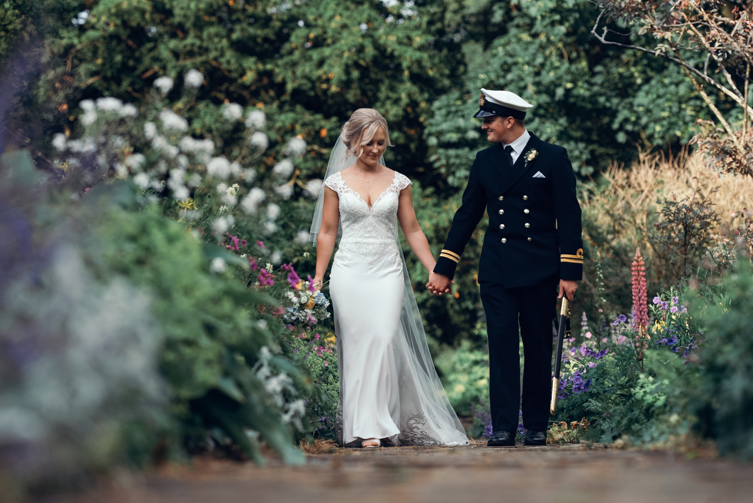 The bride and groom taking a relaxing walk through the amazing gardens at Askham Hall