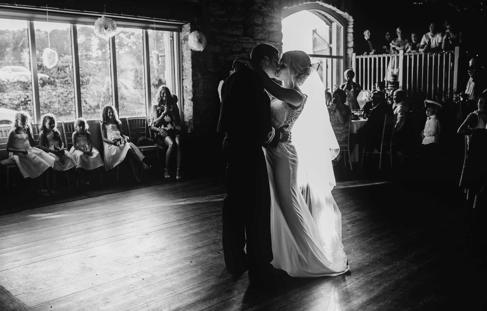 The bride and groom having the first dance with beautiful side light coming in through the side window at Askham Hall