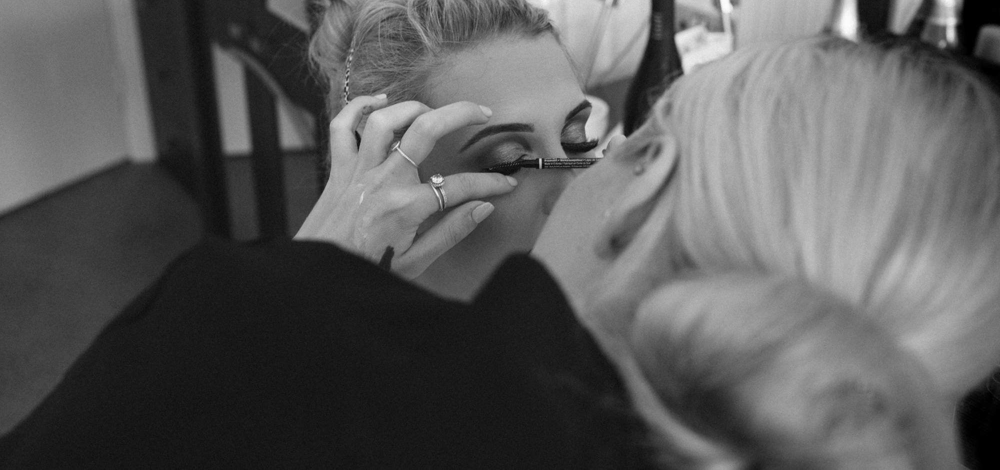 Black and white image of the bride having her eye makeup applied