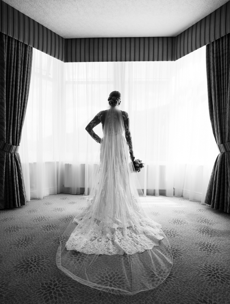 The bride standing in the bay window showing the back of her wedding dress