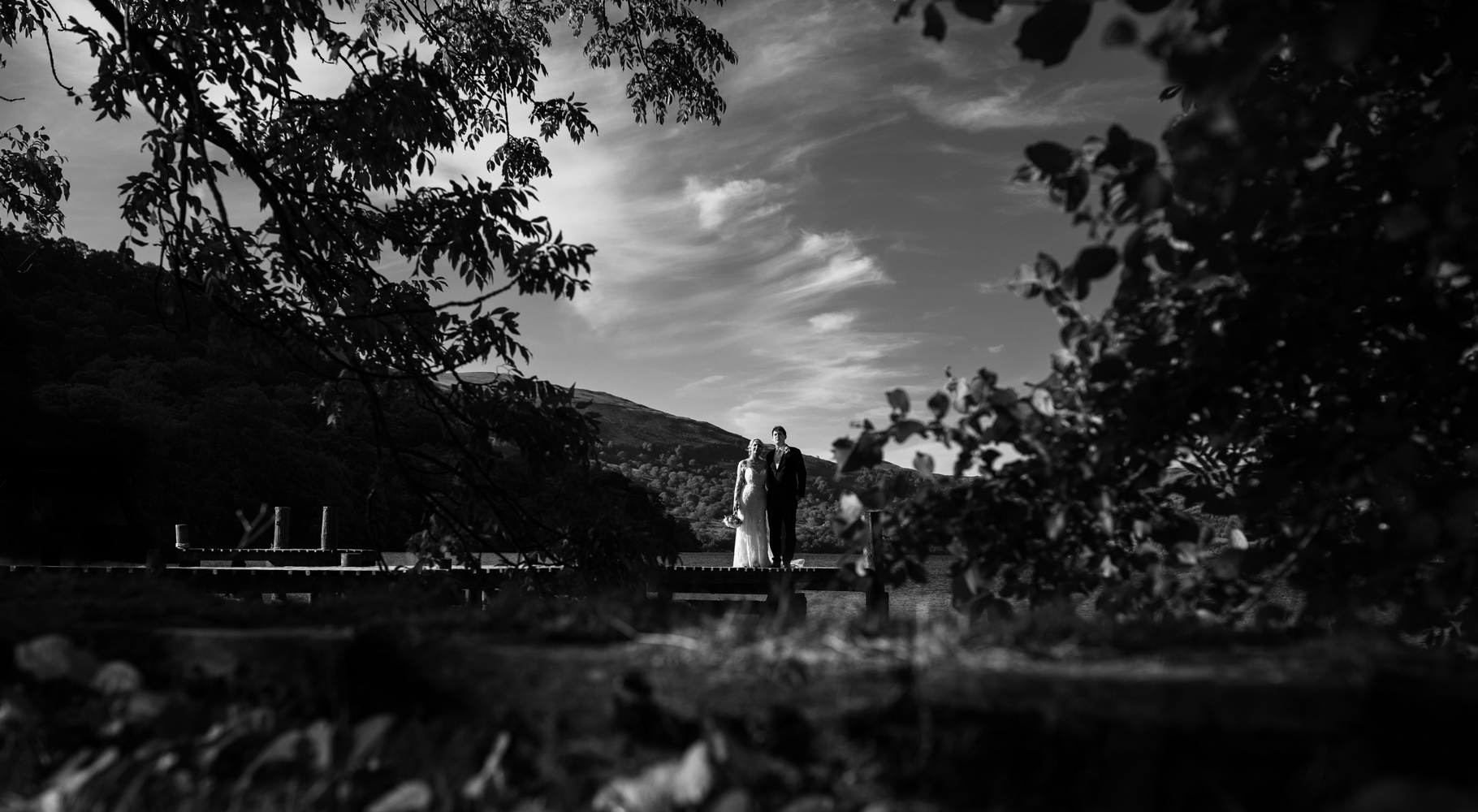 Black and white image of the bride and groom standing on the jetty taken through the trees at the waters edge