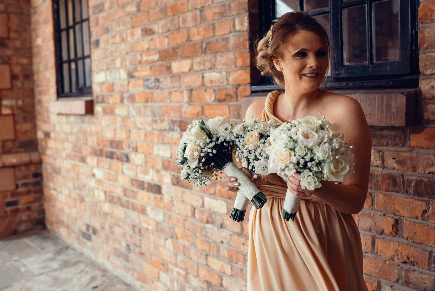 The maid of honour standing outside holding the brides bouquet awaiting her arrival at Crabwall Manor Hotel