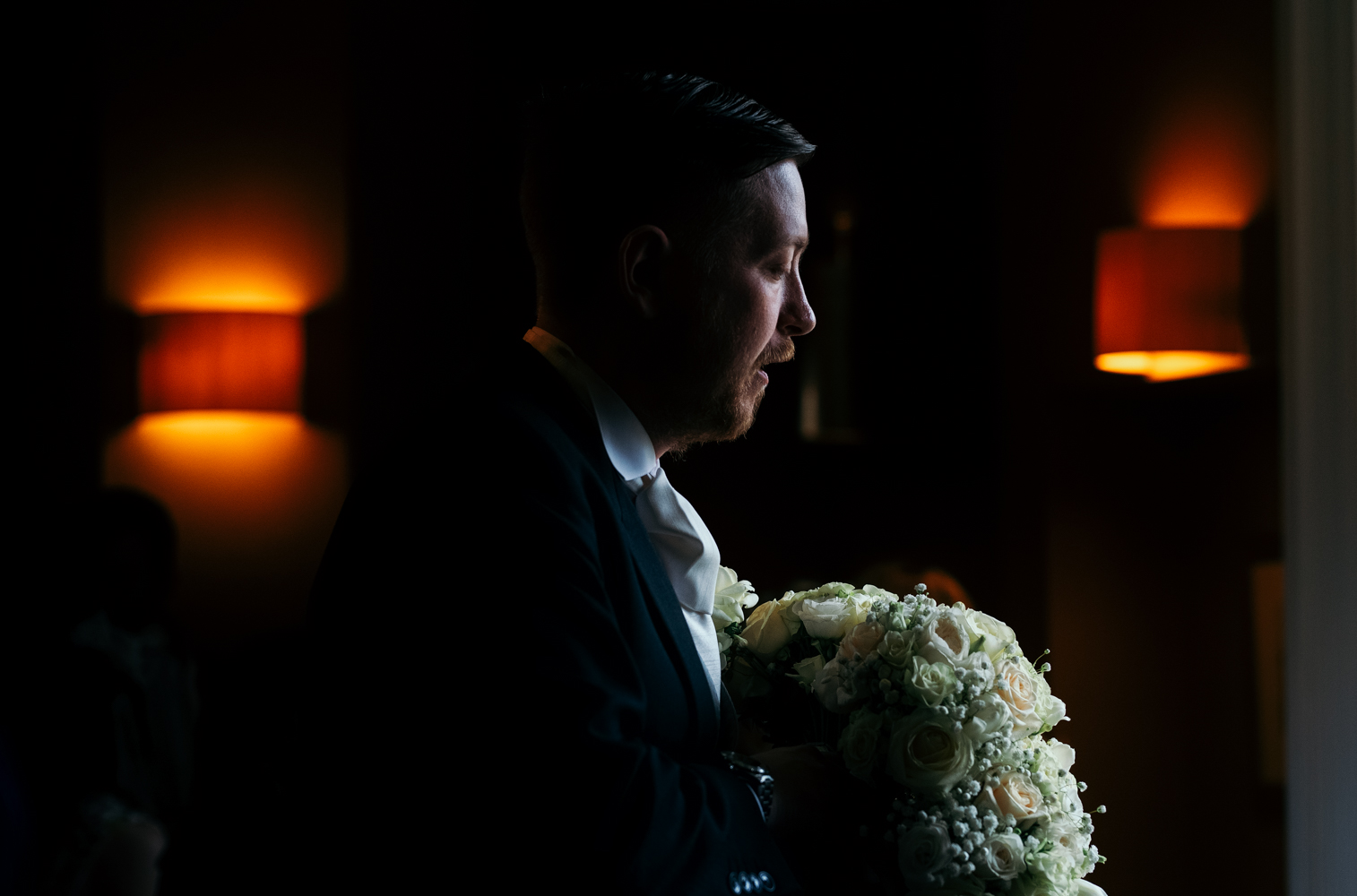 A dark and moody photo of the groom inside the wedding venue holding the flowers