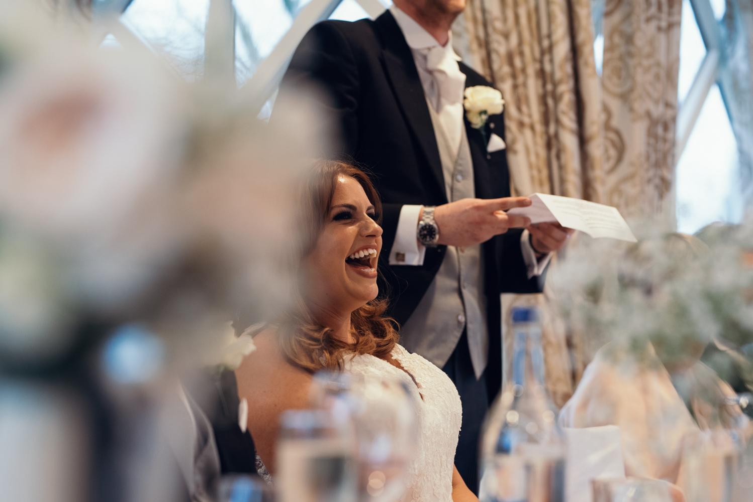 The bride laughing at one of the grooms joke during the speeches