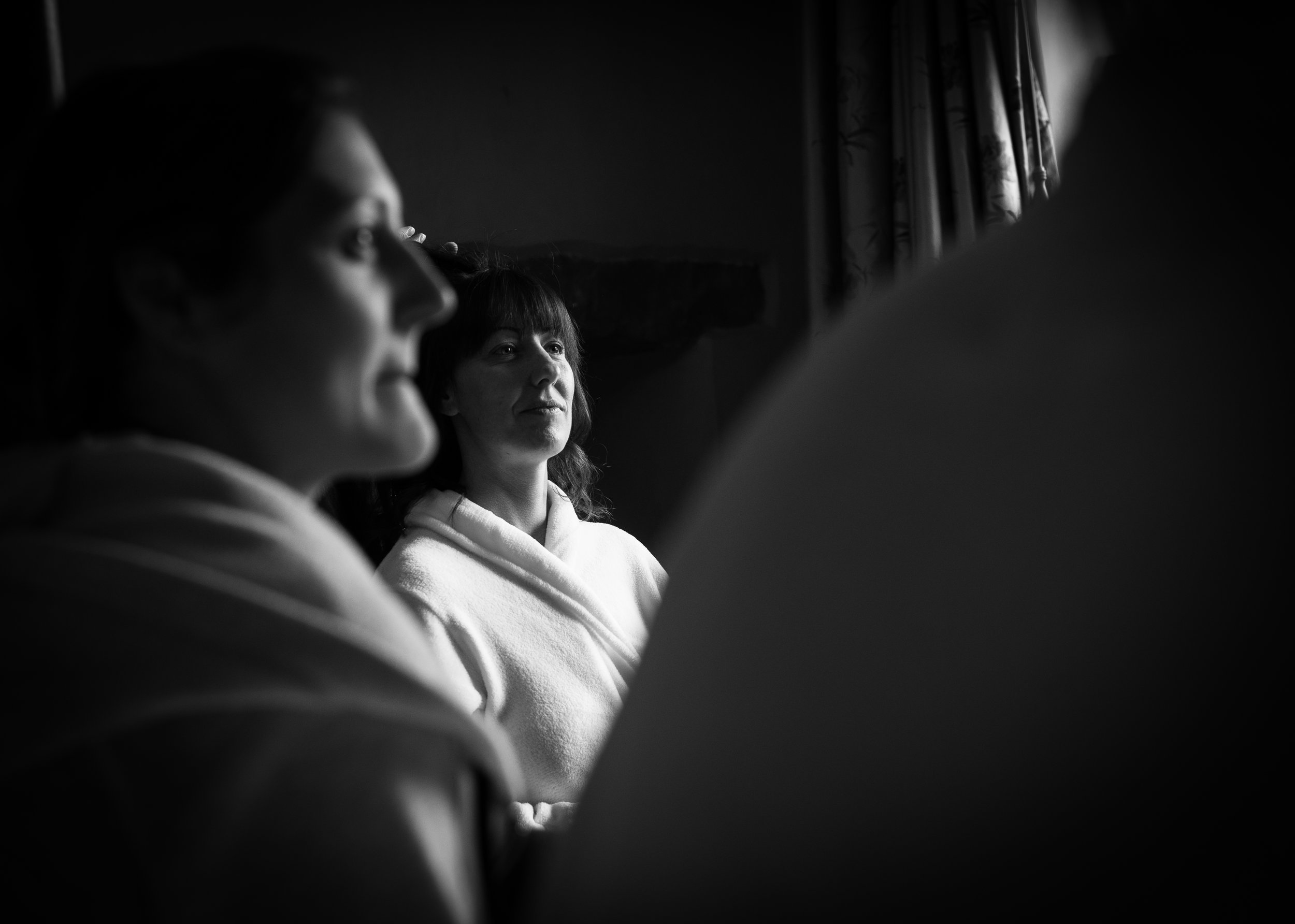 Black and white photo of the bride sitting having hair and makeup done