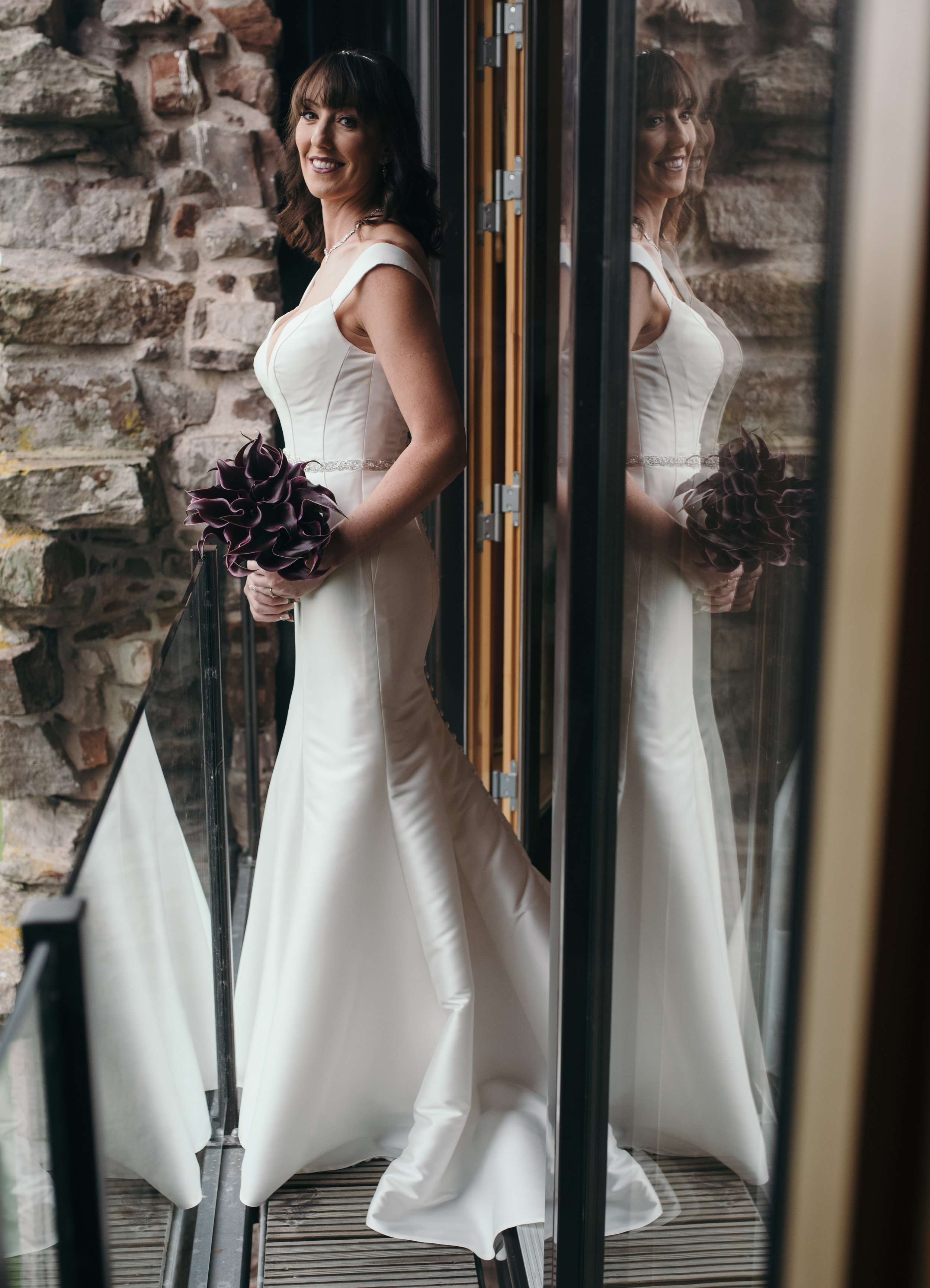 The bride standing on the balcony looking back into the bedroom