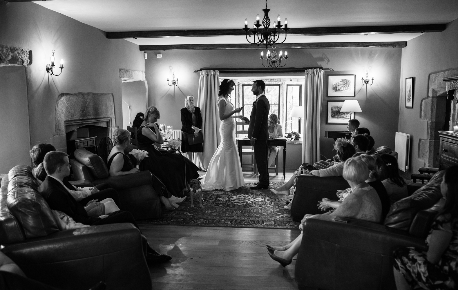 Black and white image from the back of the room while the bride and groom exchange their wedding vows