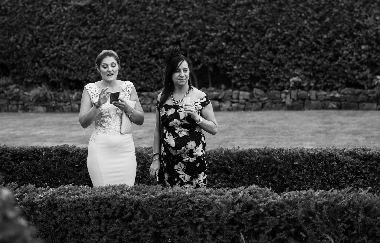 Black and white image of two of the wedding guests taking photos during the drinks reception