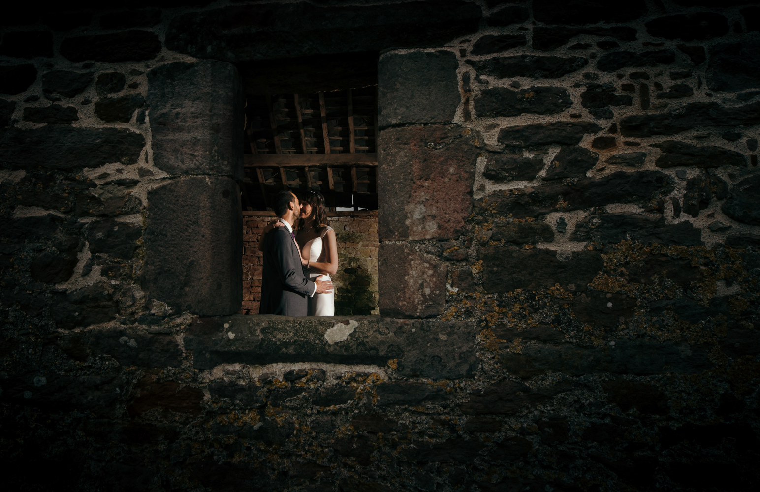 The bride and groom standing in a window having a cuddle