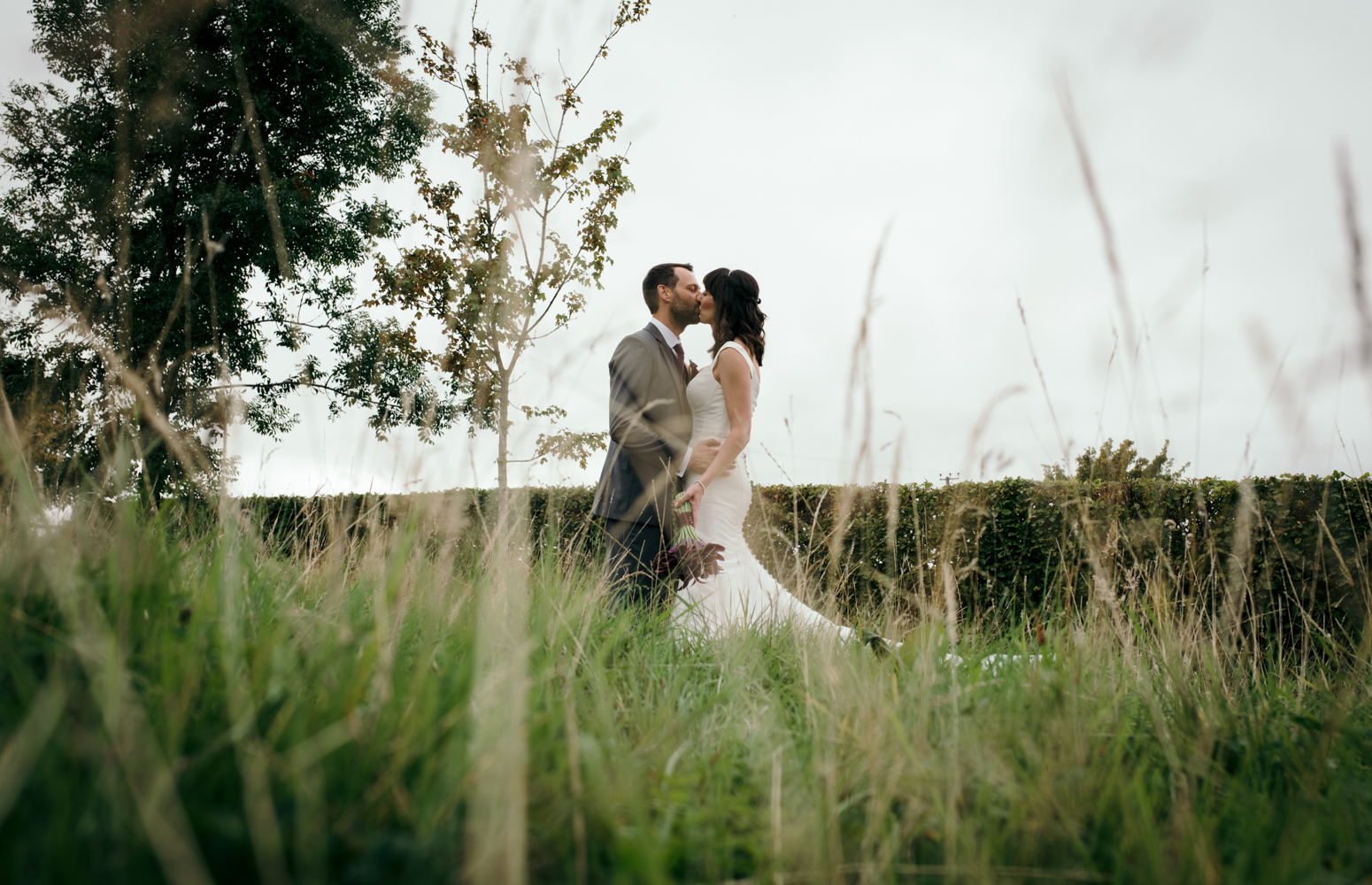 The bride and groom standing in the garden during a portrait session