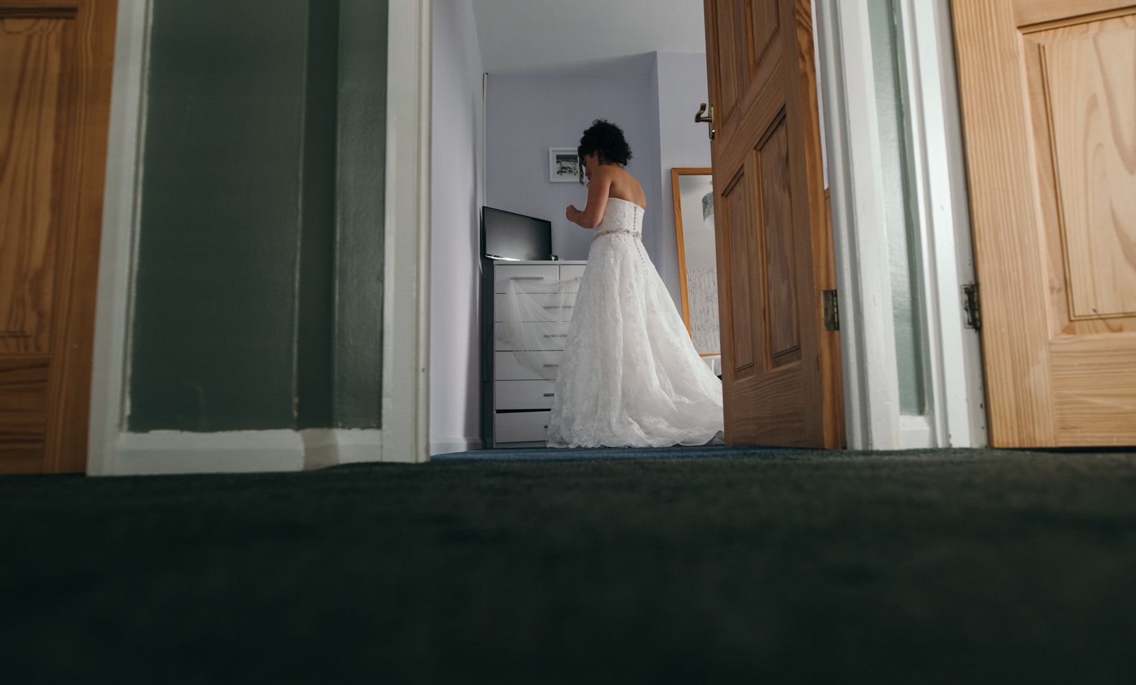 The bride getting into her wedding dress taken from the top stair looking back into the bedroom