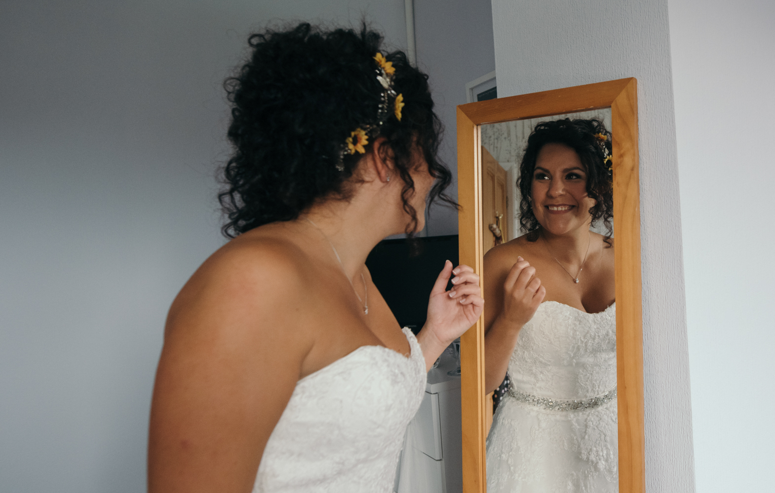The bride admiring her look in the mirror wearing her wedding dress