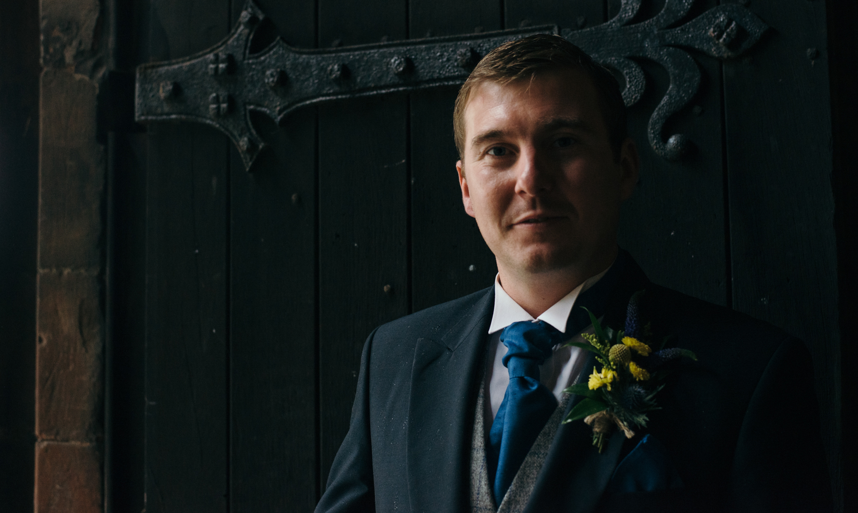 The groom portrait standing in the doorway waiting to welcome wedding guests