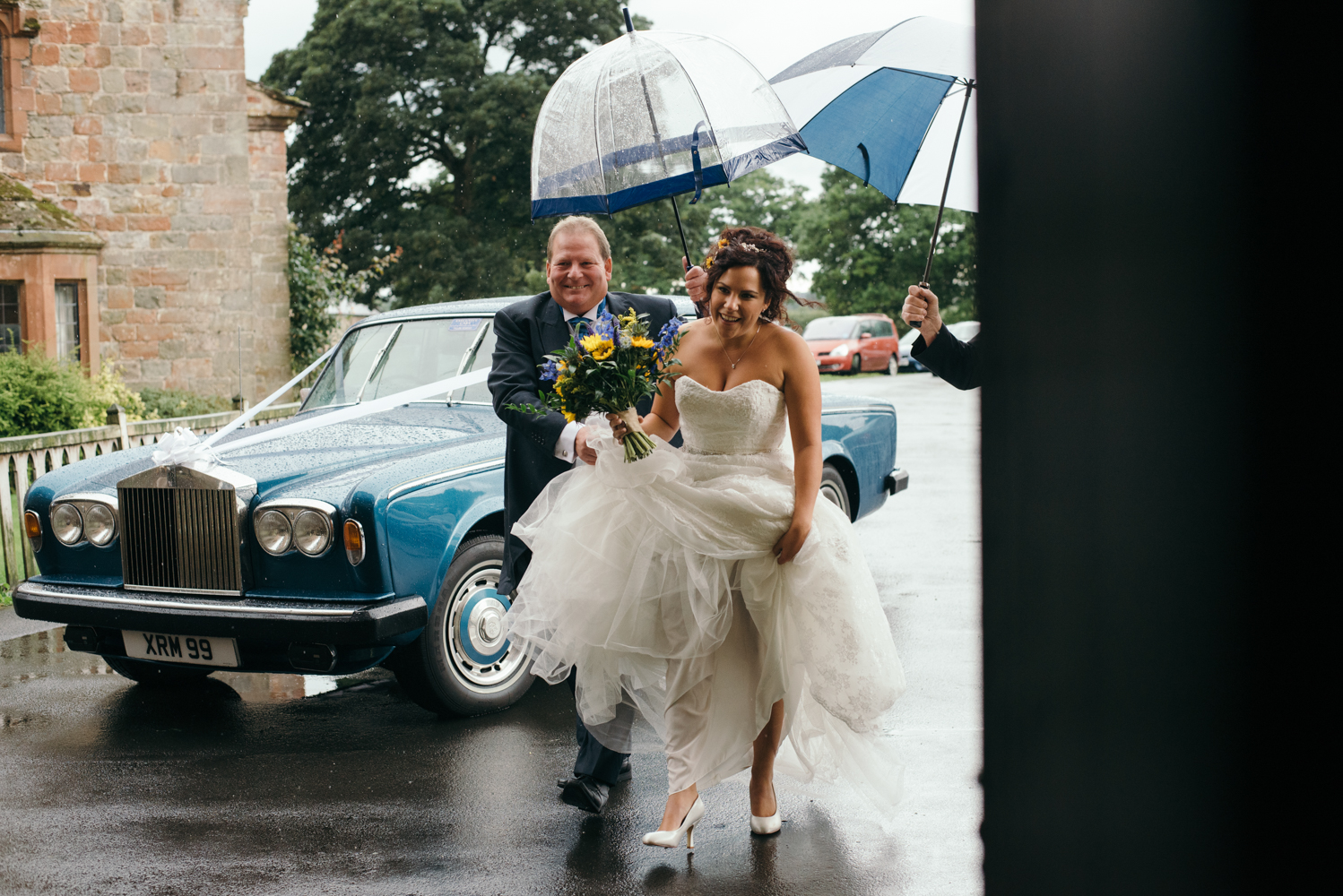 The bride braving the rotten weather arriving with her father