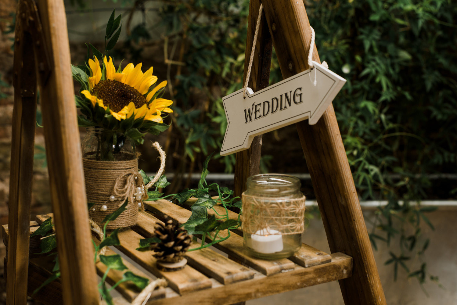 A decorated stepladder with lots of flowers and candles