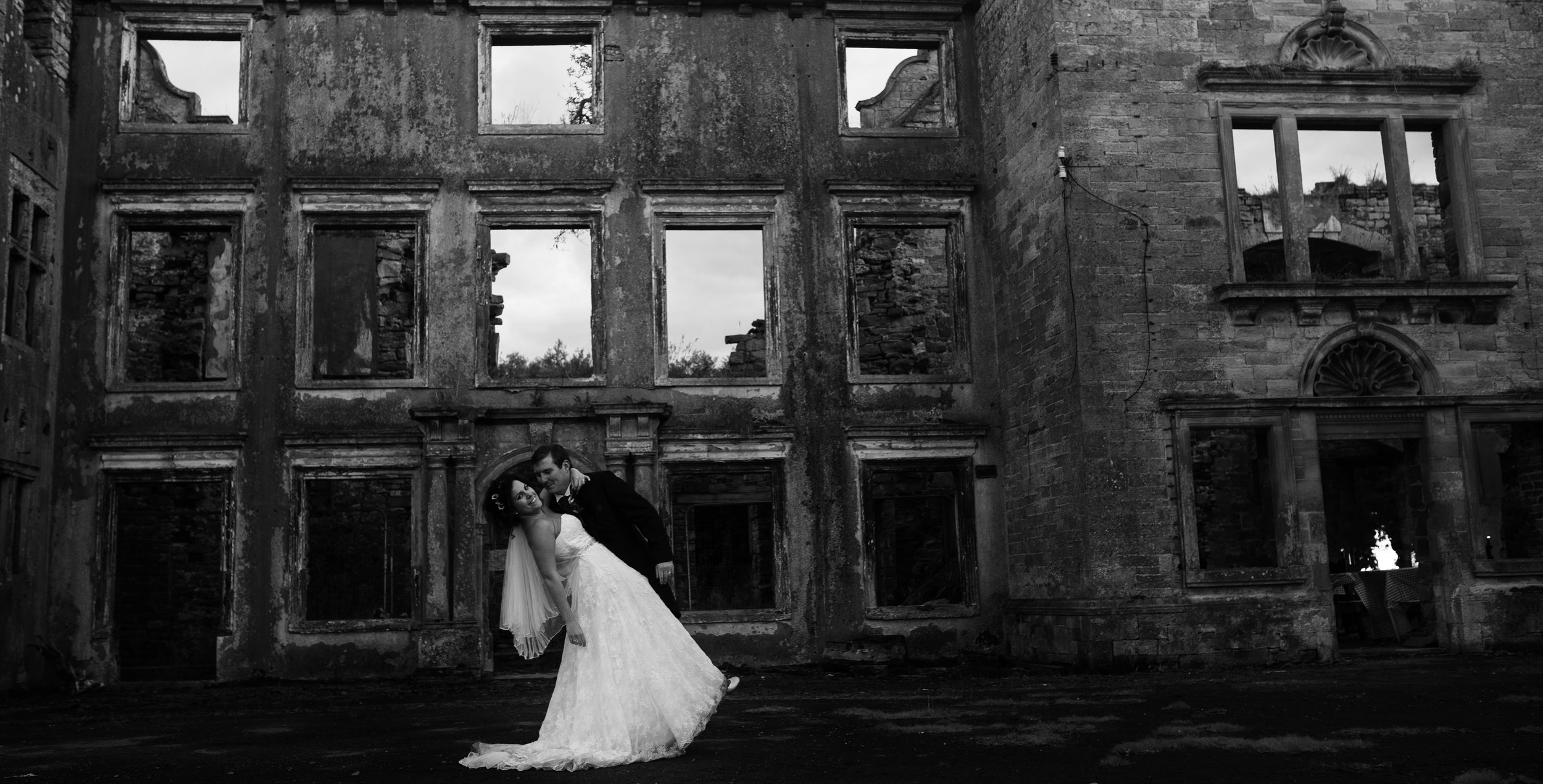 The bride and groom black and white portrait with the building in the background