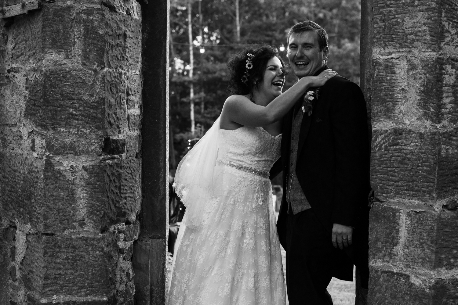 Black and white image of the bride and groom making light of the fact that they are having portrait photos