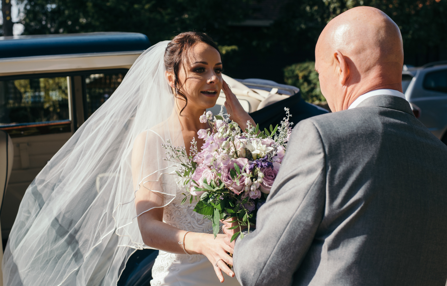 The bride and her father as she gets out of the car at church