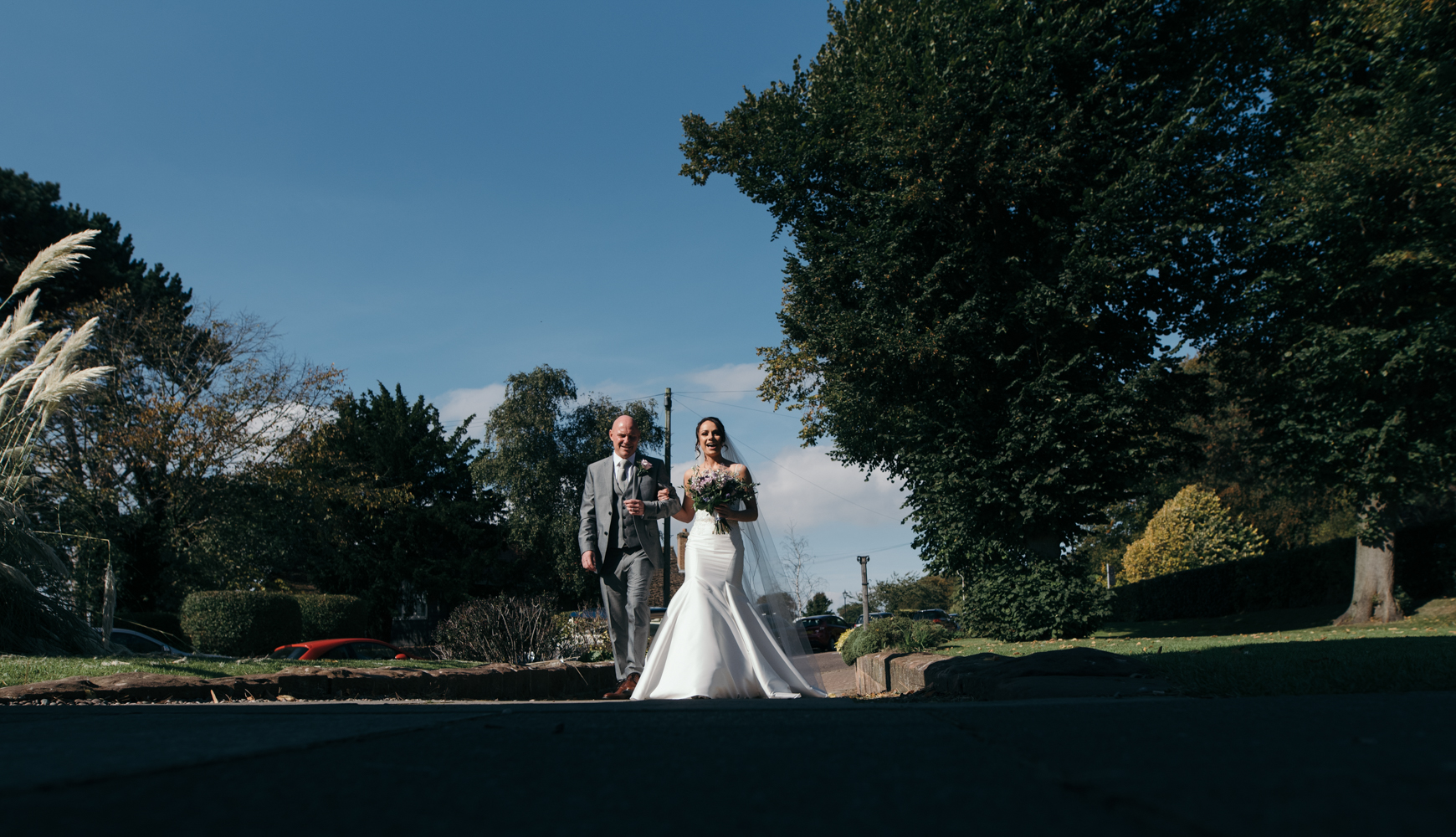 The bride and her father walking up the path to church