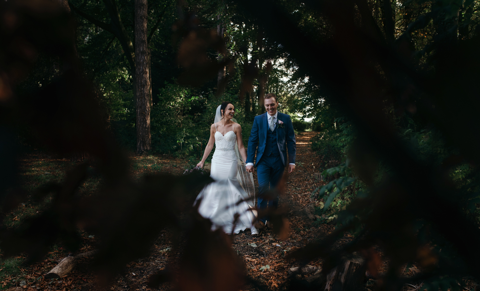 The bride and groom walking in the woods at Inglewood Manor
