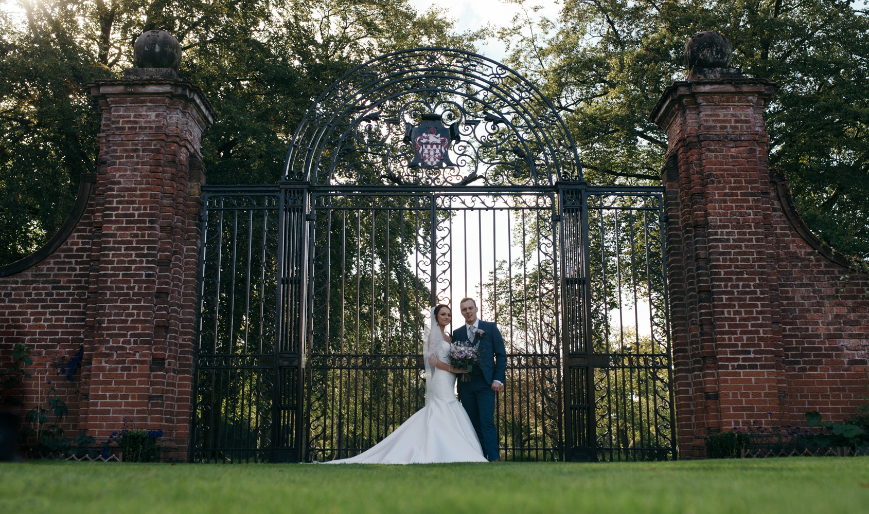 The bride and groom posing in front of the beautiful wrought iron gates at Inglewood Manor