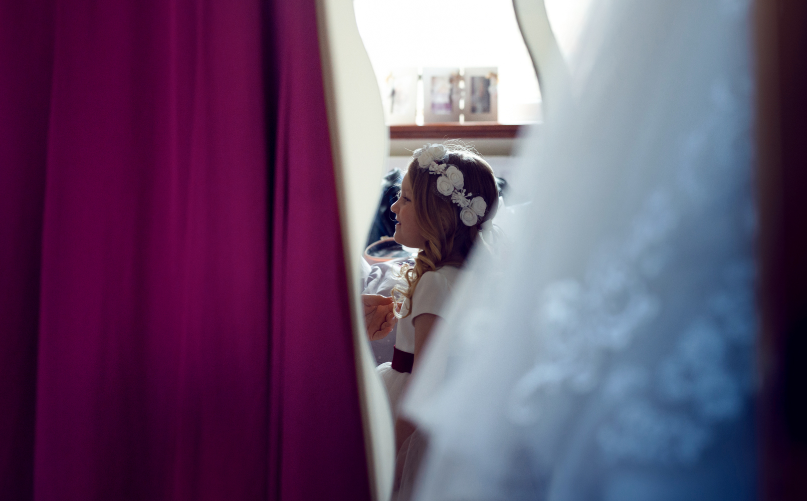 A little bridesmaid looking at the bride in her wedding dress