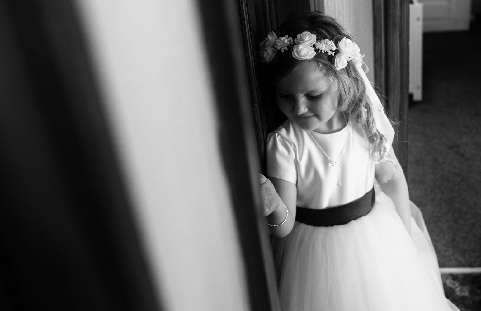 Black and white photo of the little bridesmaid waiting for the bride to get into her dress