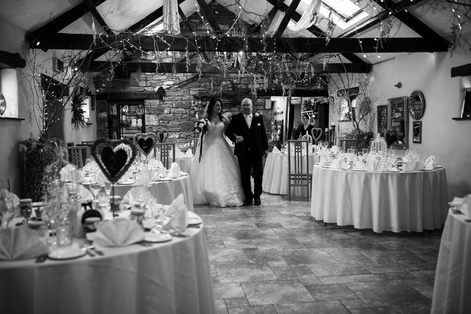 Black and white photo of the bride and her father walking towards the registrars