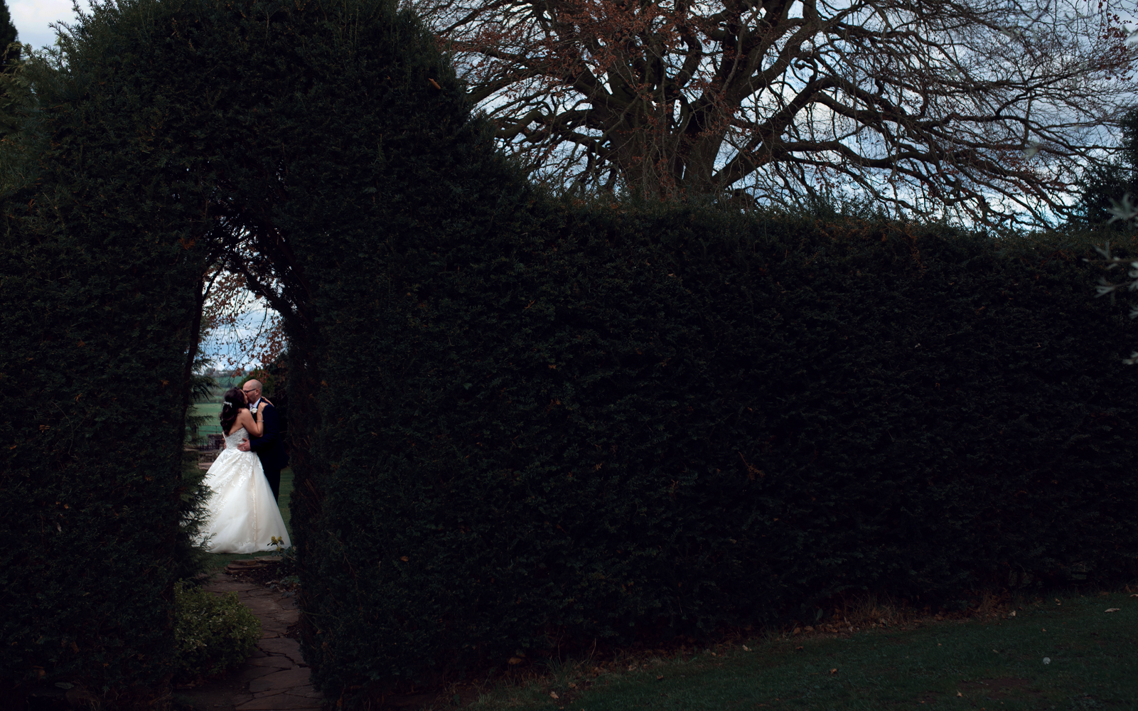 The bride and groom through a gap in the hedge during couples portrait session