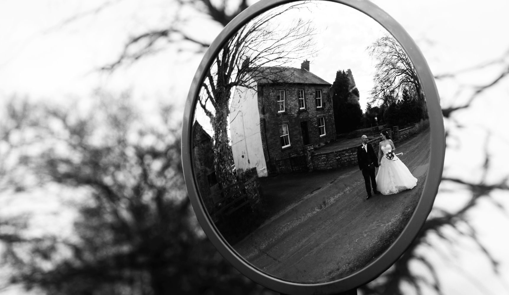 A black and white photo of the bride and groom reflected in a mirror