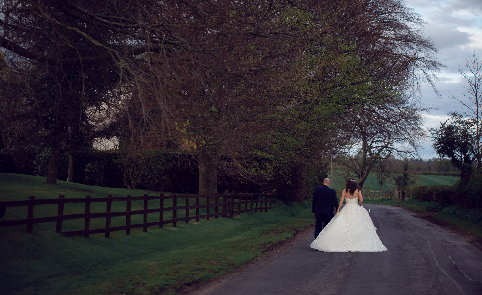 The bride and groom walking down the road during couples portrait session