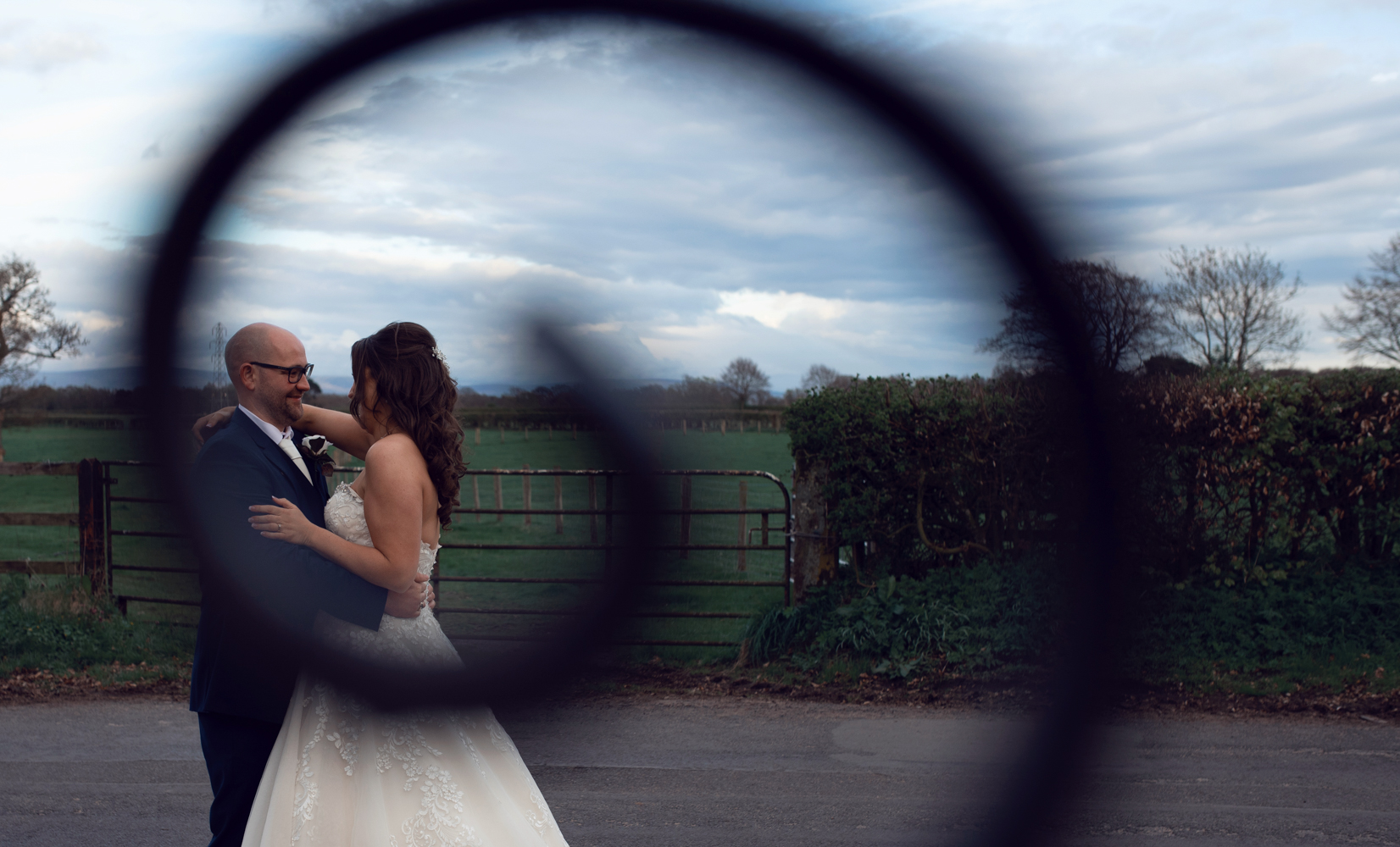 Photo of the bride and groom taken through a wrought iron gate swirl