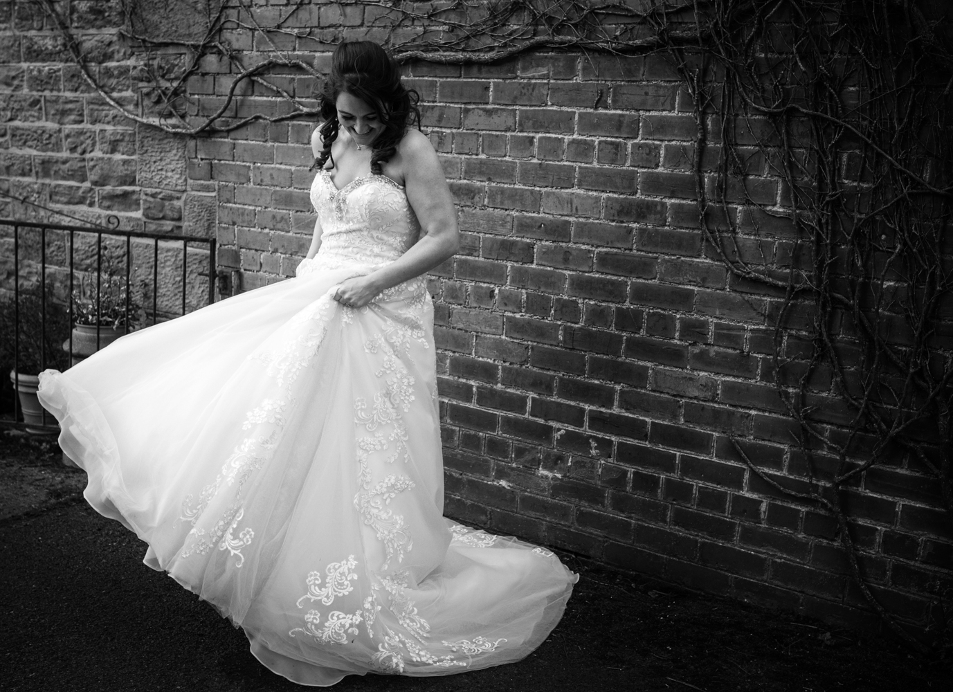 Black and white photo of the bride swirling her wedding dress around