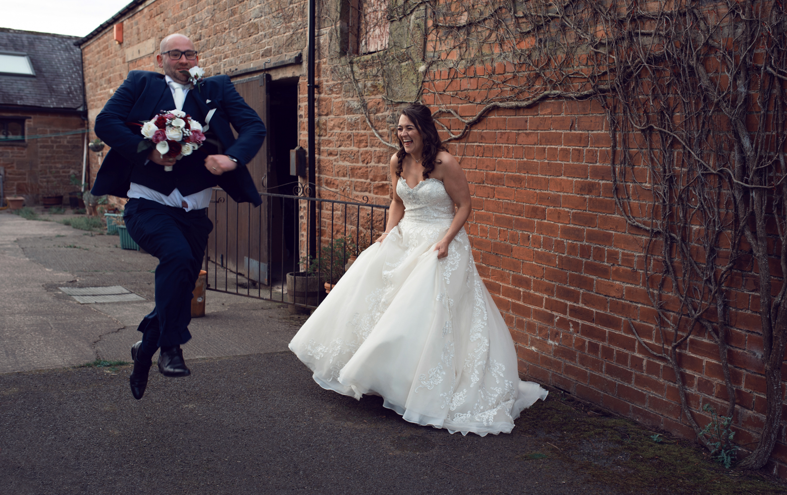 The bride laughing as the groom runs and jumps in front of her