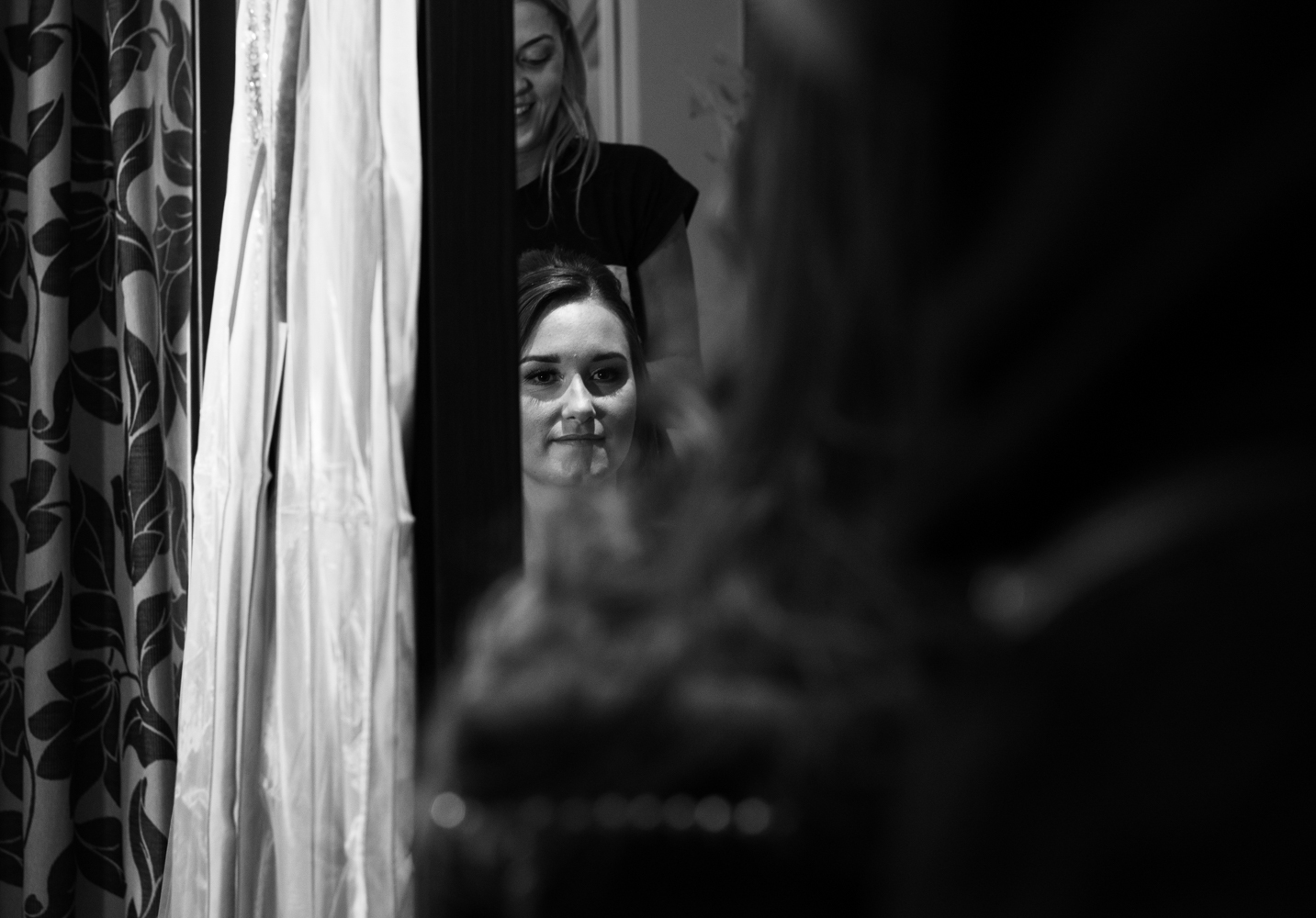 A black and white image of one of the bridesmaids during morning preparations
