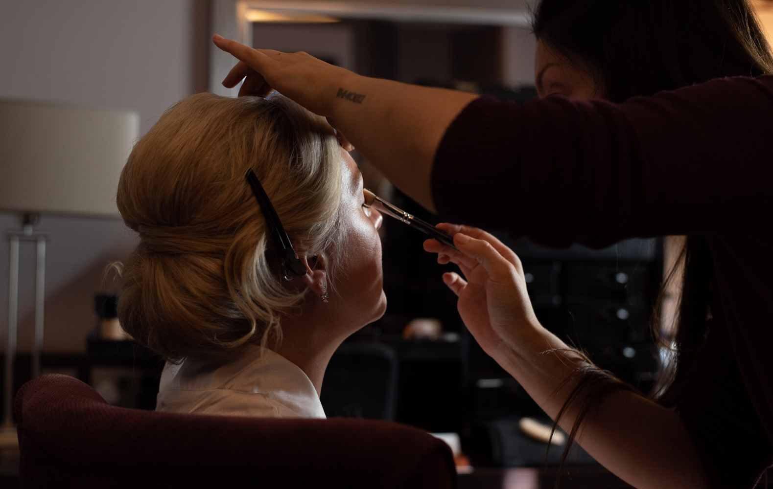 The bride having her makeup applied during morning preparations