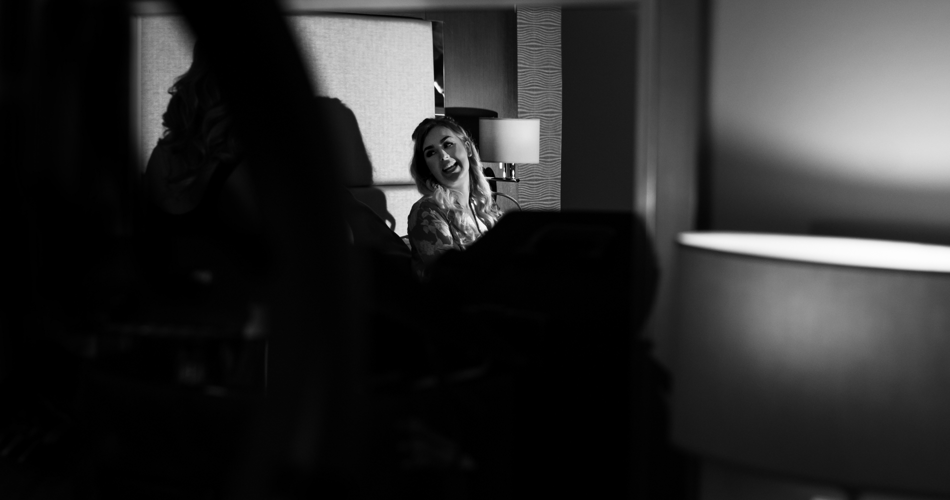 A black and white photo of one of the bridesmaids laughing during preparations