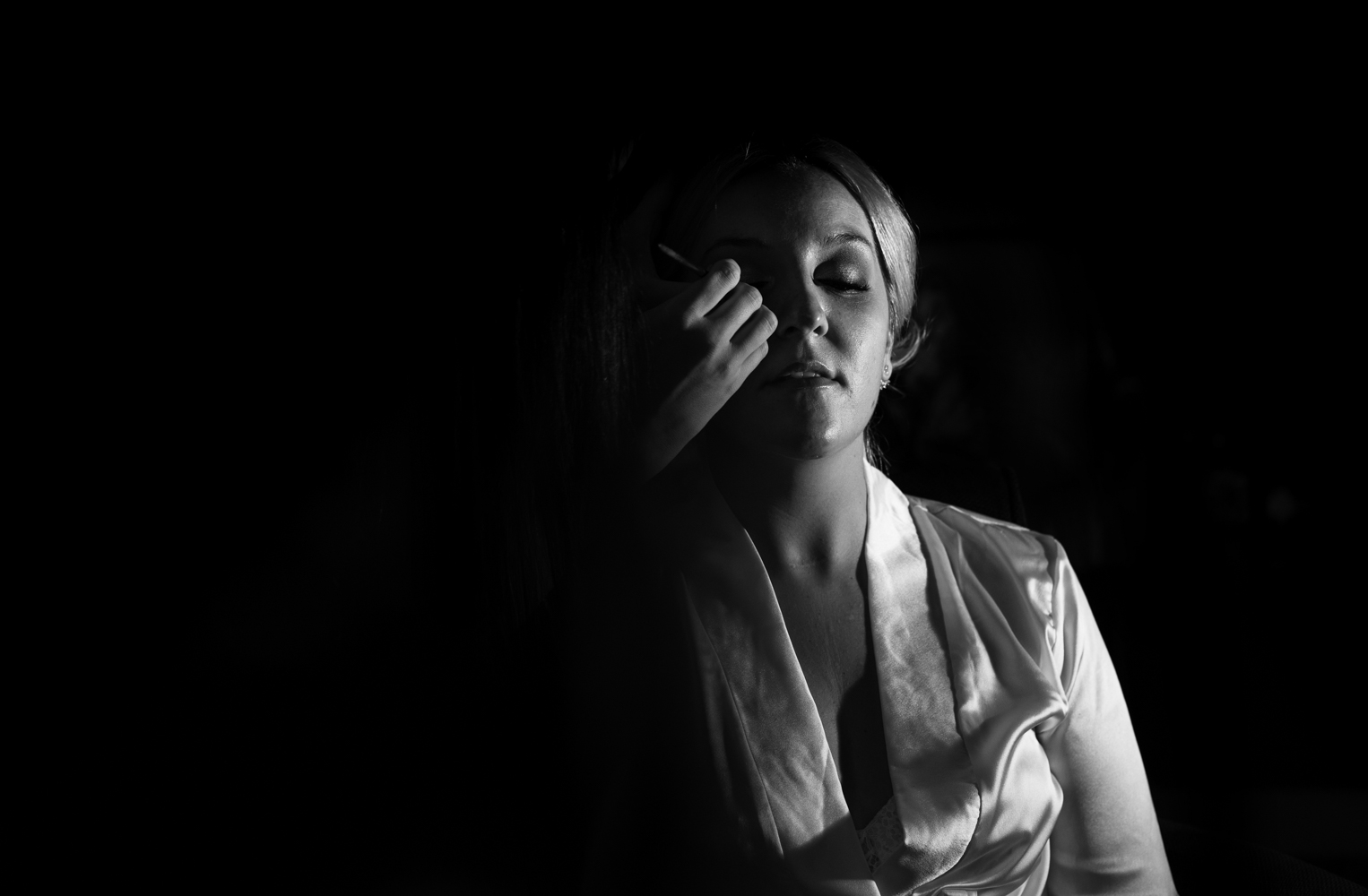 A black and white photograph of the bride during her makeup