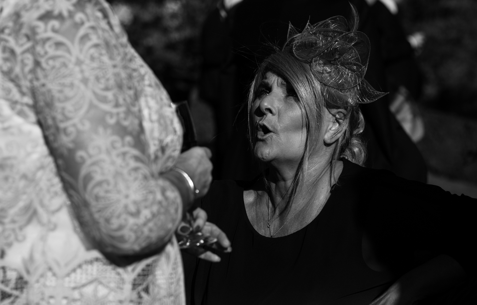 A black and white photo of one of the wedding guests during the drinks reception